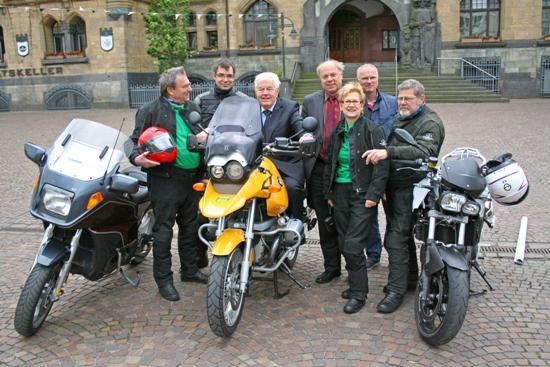 Stellvertretender Bürgermeister Ferdinand Zerbst (3.v.l.) sitzt auf dem Motorrad von Claus Kauba von Gaelic-Motorbike-Tours (l.) und stellt mit Dezernent Georg Möllers (4.v.l.) und Karl-Heinz Broß, stellvertretender Leiter der BRÜCKE (2.v.r., hinten), gemeinsam mit dem Team der Gaelic-Motorbike-Tours die Fahrt nach Schmalkalden anlässlich der 25-jährigen Städtepartnerschaft vor.