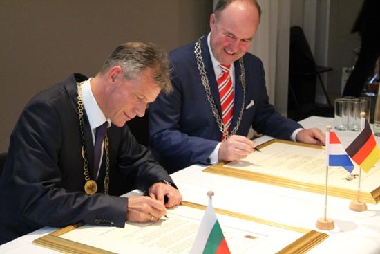 Recklinghäuser Bürgermeister Christoph Tesche (l.) und Dordrechts Bürgermeister Dr. Arno Brok unterzeichnen die Urkunde zur Bestätigung der Städtepartnerschaft zwischen Dordrecht und Recklinghausen