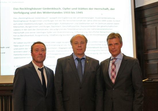 Bürgermeister Christoph Tesche (r.) stellt gemeinsam mit dem Ersten Beigeordneten Georg Möllers (2.v.l.) und VHS-Leiter Jürgen Pohl (l.) das Online-Gedenkbuch vor.