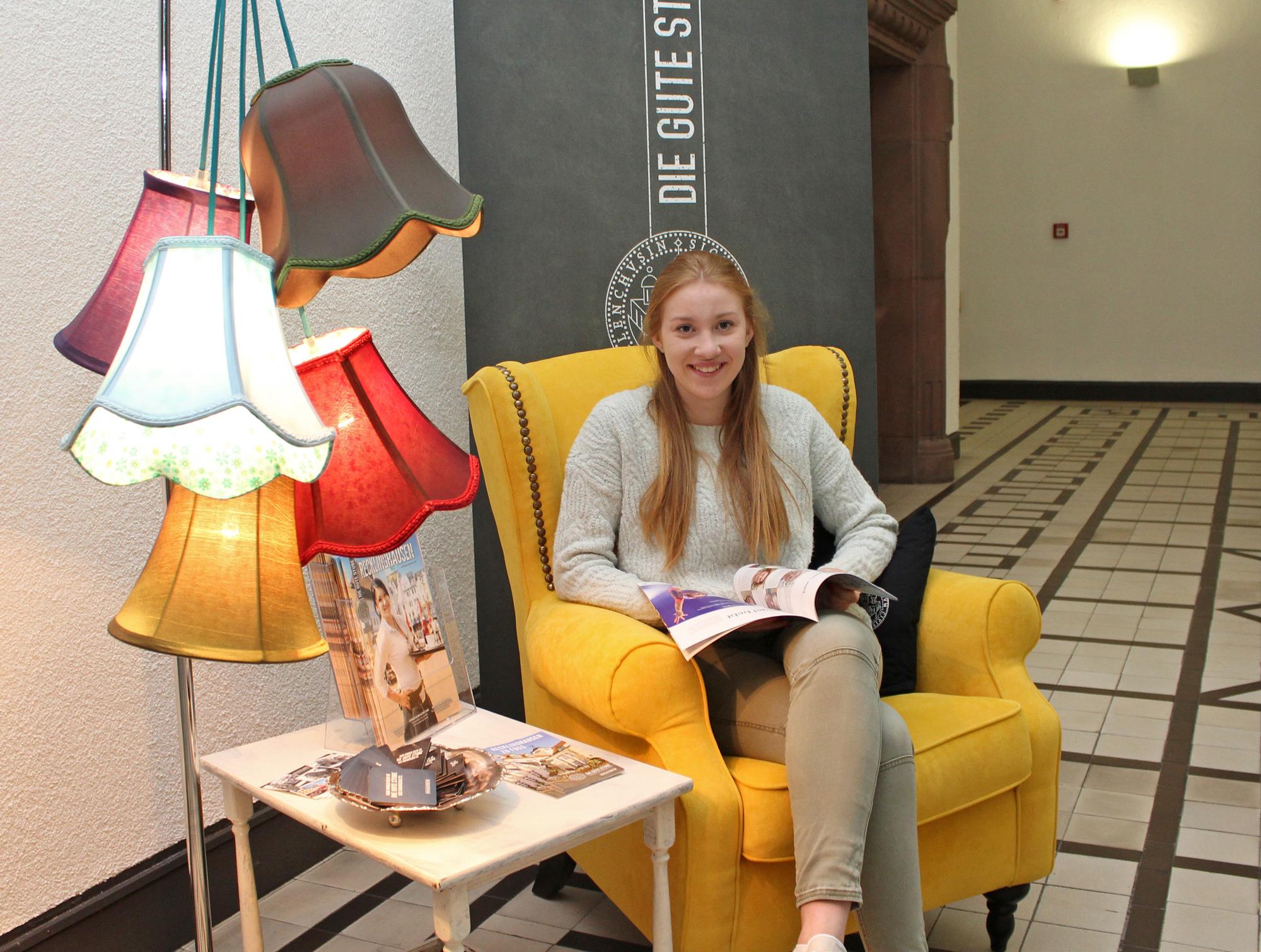 Stadtmarketing-Praktikantin Alicia Müller probiert den Ohrensessel der Info-Ecke aus.
