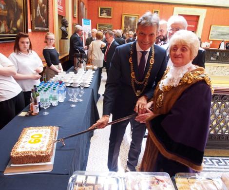 """Bürgermeister Christoph Tesche und Bürgermeisterin Margaret McManus haben die """"Jahrestorte"""" anlässlich des 60-jährigen Jubiläums der Städtepartnerschaft im Harris-Museum angeschnitten."""
