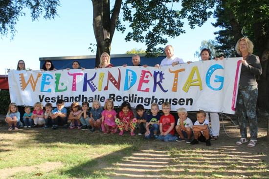 Gemeinsam freuen sich der Erste Beigeordnete Georg Möllers (3. v. r.), Fachbereichsleiter Volker Hülsmann (4. v. r.) und Mitarbeiterin Tanja Alshut (l.), Christel Tophoff von UNICEF (r.) , Denise Anton vom Kinderschutzbund (4. v. l.) sowie die Kinder und Erzieherinnen des Familienzentrums an der Hohenzollernstraße auf den Weltkindertag in der Vestlandhalle.