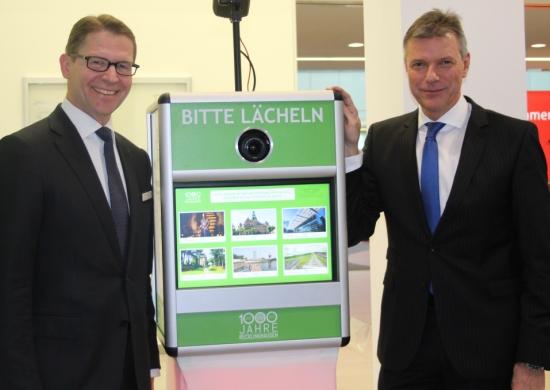 von rechts: Bürgermeister Christoph Tesche und Dr. Michael Schulte von der Sparkasse mit der Fotobox zum Stadtjubiläum.