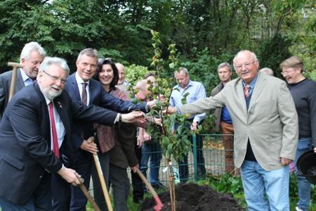 Pressefoto - In der Kleingartenanlage Bergmannssonne pflanzte Bürgermeister Christoph Tesche - linke Seite, 3. von links - zusammen mit vielen Gästen des Bürgermeisterempfangs einen Mispelbaum als Zeichen für Freundschaft, Toleranz und Liebe.
