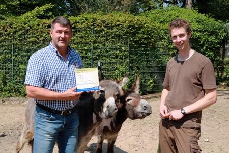 Pressefoto - Stefan Klinger  -l.- Bereichsleiter Tierpark bei den KSR, Lukas Gers, leitender Tierpfleger im Tierpark, und die beiden Eselstuten Finja und Romena freuen sich über die offizielle Plakette, die den Tierpark Recklinghausen als Mitglied der DTG ausweist.