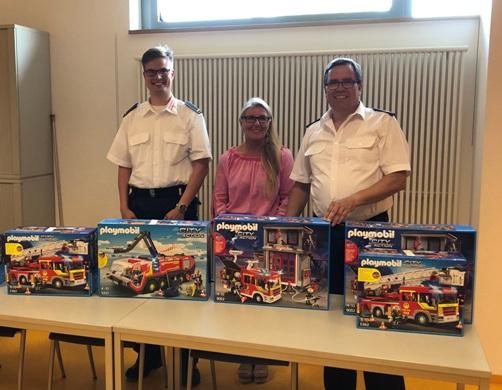 Daniel Richmann, stellvertretender Fachbereichsleiter Feuerwehr, Jördis Kolar von der Provinzial Versicherung und Andreas Schulte-Sasse, stellvertretender Leiter der Feuerwehr, mit den Playmobil-Sets, die es bei der Tombola zu gewinnen gab.