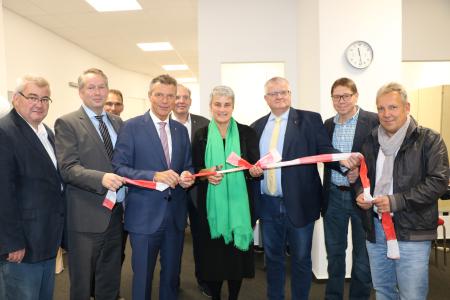 Bildzeile - Bürgermeister Christoph Tesche -. 4.v.l. - hat gemeinsam mit Frau Dr. Iris van Eik symbolisch das Absperrband durchgeschnitten - begleitet von Mitarbeitern aus der Verwaltung, der Verbraucherzentrale und der städtischen Wohnungsgesellschaft sowie Ratsmitgliedern aus CDU und SPD.