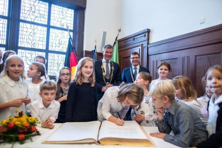 Sichtlich Spaß hatten die Bürgermeister Christoph Tesche und Thomas Kaminski beim Eintrag ins Goldene Buch mit den Mitgliedern des Kinder- und Jugendchors der städtischen Musikschule.