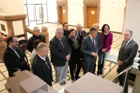 Pressefoto - Stadtarchivar Dr. Matthias Kordes gab Bürgermeister Christoph Tesche und Vertretern aus Verwaltung und Politik einen ersten Einblick in die neue Ausstellung im Rathaus-Foyer.