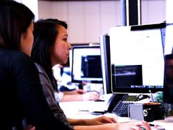 Das Bild zeigt zwei Frauen, die vor einem Bildschirm sitzen.