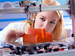 Das Bild zeigt eine Frau, die einen 3D-Drucker bei der Arbeit beobachtet.