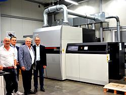 Bürgermeister André Dora lässt sich von Vinzenz, Mark und Jürgen Schmidt bei der Firma Wirtz Druck die neue digitale Druckmaschine erklären.