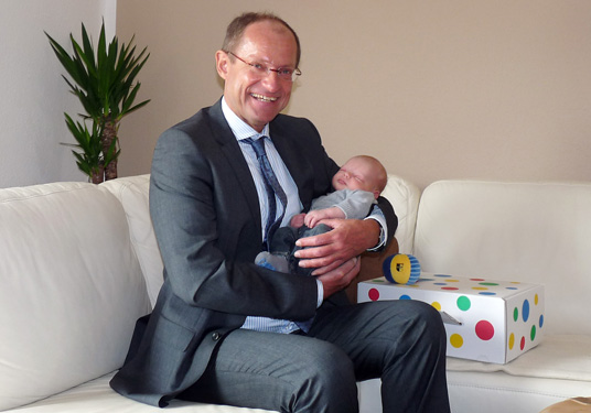 Das Bild zeigt Bürgermeister Ulrich Roland mit dem Baby Maximilian