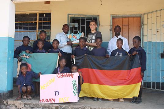 Das Bild zeigt, wie Marvin Wetekam dem stellvertretenden Schulleiter Mr. Ndambo das Gastgeschenk der Pestalozzischule überreicht