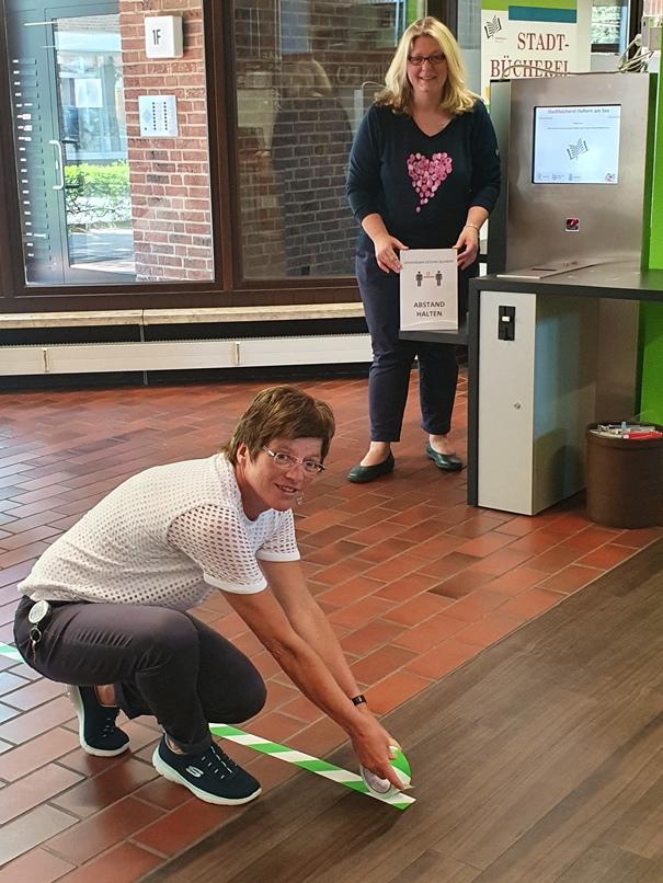 Claudia Schäpers (li.) und Andrea Coenen-Brinkert treffen die Vorbereitungen, damit sie ab Dienstag wieder die Bücherei öffnen können.