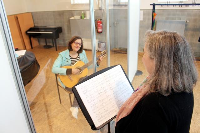 Durch Plexiglas getrennt: Musikschulleiterin Verena Voß (re.) und Mitarbeiterin Katharina Hörsting demonstrieren die Maßnahmen zur Hygiene für die Musikschule. Foto: Stadt Dülmen/Siemes