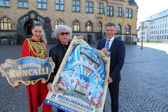 Das Plakat zur Saisonpremiere zeigen Bürgermeister Christoph Tesche (v.r.), Circusdirektor Bernhard Paul und Doro Kipp von Circus Roncalli