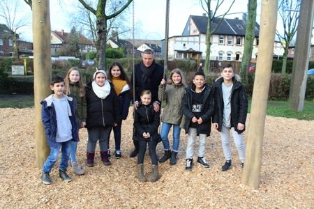 Pressefoto - Bürgermeister Christoph Tesche und die Kinder der Grundschule Hochlarmark freuen sich über die neue Schaukel am Standort Westfalenstraße.