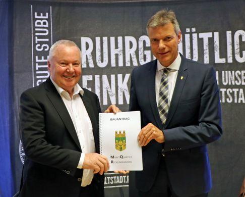 Gerd Rainer Scholze überreicht Bürgermeister Tesche symbolisch den Bauantrag.