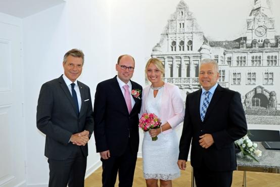 Bürgermeister Christoph Tesche, links, und Standesamtsleiter Martin Groll, rechts, mit Nadine Dreyer und Stefan Franzgrote, einem der ersten Brautpaare, die im neuen Trauzimmer des sanierten Rathauses heiraten konnten.
