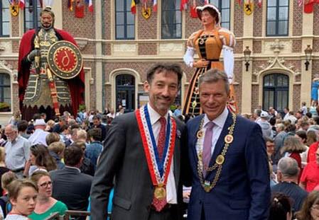 """Bürgermeister Christoph Tesche (r.) verfolgte gemeinsam mit seinem Amtskollegen Frédéric Chéreau (l.) die Parade zum Stadtfest """"Fêtes de Gayant"""" in der französischen Partnerstadt."""
