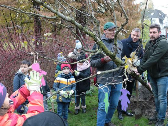 """Die Kinder der evangelischen Tageseinrichtung """"Maybacher Heide"""" pflanzten gemeinsam mit Bürgermeister Christoph Tesche (Mitte) einen Judasbaum für die Kinderrechte. Tatkräftig zur Hand gingen ihnen dabei Mitarbeiter des KSR."""