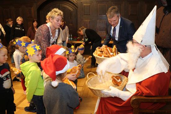 Der Nikolaus und Bürgermeister Christoph Tesche verteilen Stutenkerle an die Kinder.