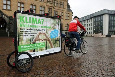 Pressefoto: Mit großen Plakatanhängern machen zwei Werbefahrer in der Stadt auf den Klimagipfel aufmerksam.