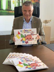 Pressefoto: Bürgermeister Christoph Tesche präsentiert das Malbuch, in dem zahlreiche Motive aus Recklinghausen darauf warten, von den Kindern ausgemalt zu werden.
