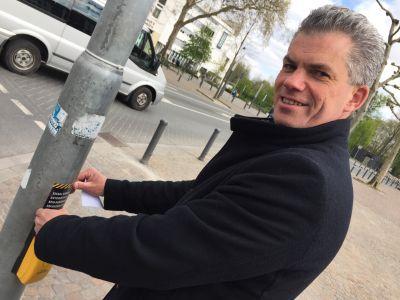Pressefoto: Axel Fritz, Abteilungsleiter Straße, klebt den Sticker an die Ampel.