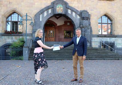 Pressefoto: Stefanie Wetterkamp bekommt den Gutschein von Bürgermeister Christoph Tesche überreicht.