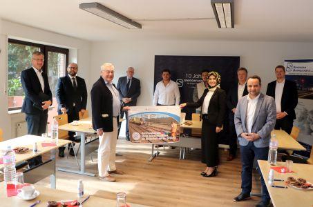 Pressefoto: VertreterInnen aus Verwaltung und Politik präsentieren gemeinsam mit der Geschäftsführung der Sendogan Bahndienste GmbH die neuen Plakate zur Aktion Wirtschaft im Fokus vor.