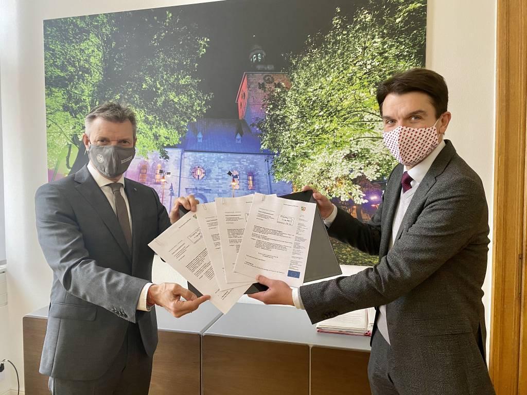 Förderbescheide für gleich vier Klimaprojekte übergab Prof. Dr. Uli Paetzel, Vorstandsvorsitzender der Emschergenossenschaft, an Bürgermeister Christoph Tesche (l.) im Recklinghäuser Rathaus. Foto: Stadt RE
