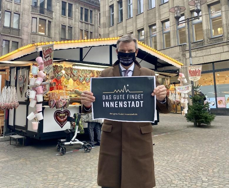 : Auf dem Altstadtmarkt in Recklinghausen präsentiert Bürgermeister Christoph Tesche den Slogan der Kampagne, mit dem die Region dafür wirbt, den lokalen Einzelhandel zu unterstützen. Foto: Stadt RE