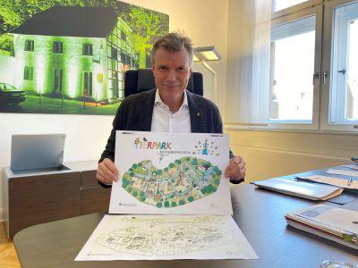 Pressefoto: Bürgermeister Christoph Tesche verschenkt Malbilder an Kinder. Das Motiv: der Tierpark im Stadtgarten. Foto: Stadt RE