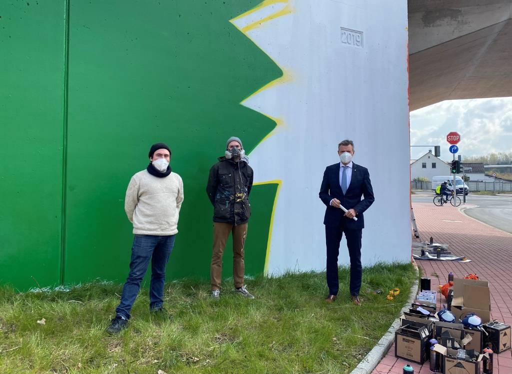 Bürgermeister Christoph Tesche (r.) machte sich vor Ort ein Bild von den Graffiti-Fortschritten an der Schlachthofbrücke. David Kory, Projektleiter bei Die Urbanisten e.V., und der Künstler Oliver Mark (v. l.) brachten ihn auf den neuesten Stand. Foto: Stadt RE