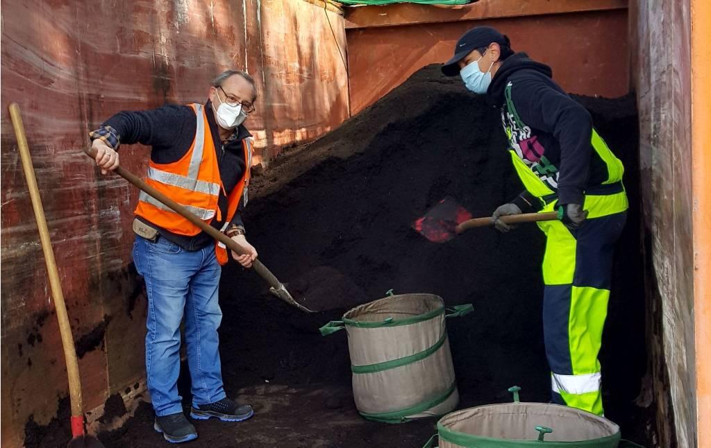 Pressefoto 1: Klaus Jagner und Simona Leibrandt schüppten den Kompost in die Behältnisse der RecklinghäuserInnen. Foto: Stadt RE - KSR