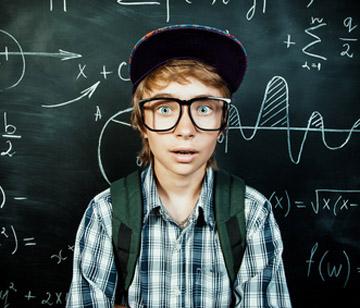 """Bild: """"School Chalkboard"""", © Andrey Kiselev, fotolia.com; Auf dem Bild: Kind vor einer Schultafel mit mathematischen Formalen und Grafiken"""