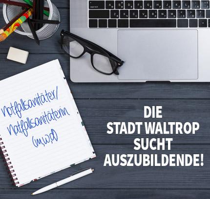 Auf dem Bild: Arbeitsplatz mit PC und Notizblock. Schrift im Bild: Die Stadt Waltrop sucht Auszubildende, Notfallsanitäter/in (m,w,d).