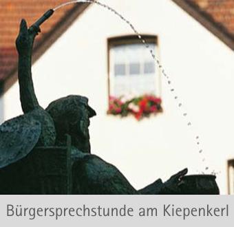 Auf dem Bild: Kiepenkerlbrunnen. Schrift im Bild: Bürgersprechstunde am Kiepenkerl; Foto: Stadt Waltrop