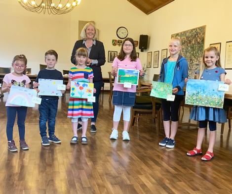 Auf dem Bild: Nicole Moenikes mit den Gewinnerinnen und Gewinnern des Kindermalwettbewerbs