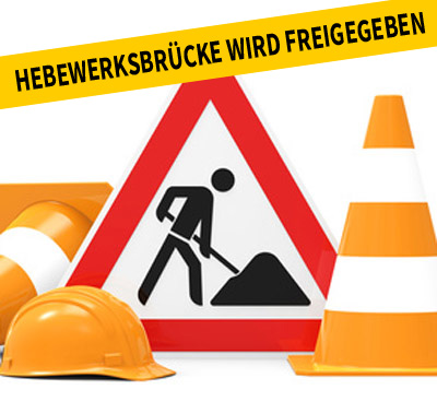 Auf dem Bild: Baustellenschild, Sicherheitshelm, Leitkegel.